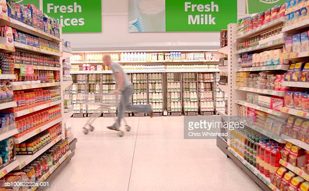 Customer riding on shopping trolley past supermarket aisle
