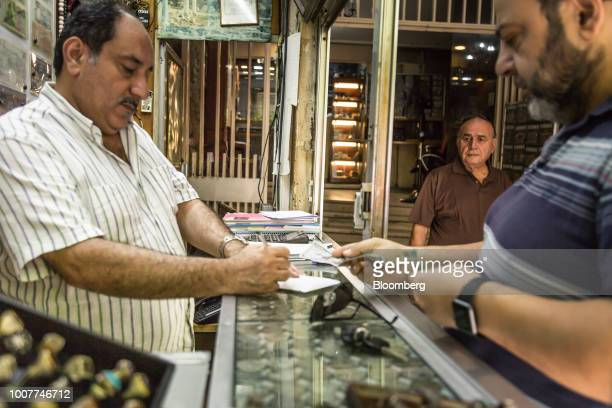 A customer right exchanges currency at a foreign currency exchange store on Hamra Street in Beirut Lebanon on Tuesday July 24 2018 Lebanonsbanks are...