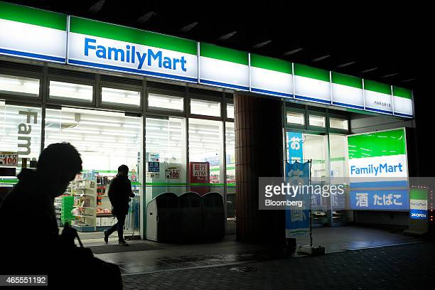 A customer right exits a FamilyMart Co convenience store at night in Tokyo Japan on Saturday March 7 2015 FamilyMart and Uny Group Holdings Co are in...
