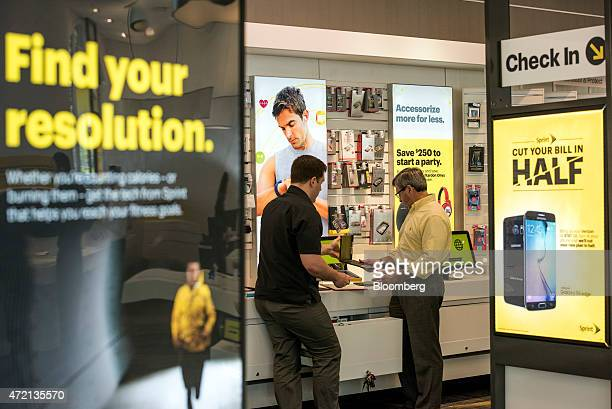 Customer, right, looks at merchandise with an employee at a Sprint Corp. Store in Palo Alto, California, U.S., on Friday, May 1, 2015. Sprint Corp....