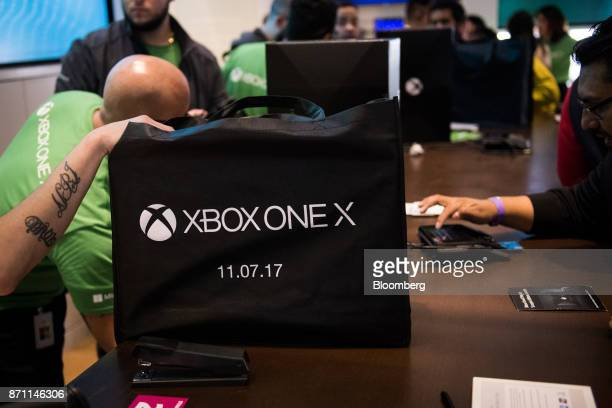 A customer right purchases an Xbox One X game console ahead of its midnight release during the Microsoft Corp global launch event in New York US on...