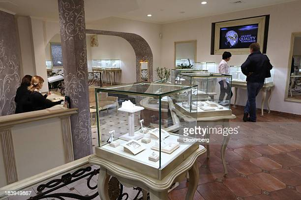 A customer right talks to an employee beyond a display of diamond jewelry inside a luxury store operated by Kristall Production Corp in Moscow Russia...