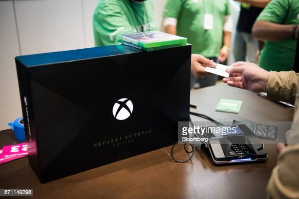 A customer right uses his credit card to purchase an Xbox One X game console ahead of its midnight release during the Microsoft Corp global launch...