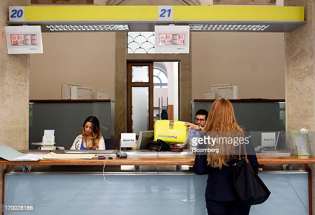A customer right waits as an employee center weighs a parcel at a service counter inside a Poste Italiane SpA post office in Rome Italy on Wednesday...