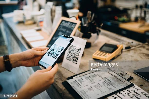 customer scanning qr code, making a quick and easy contactless payment with her smartphone in a cafe - restaurante imagens e fotografias de stock