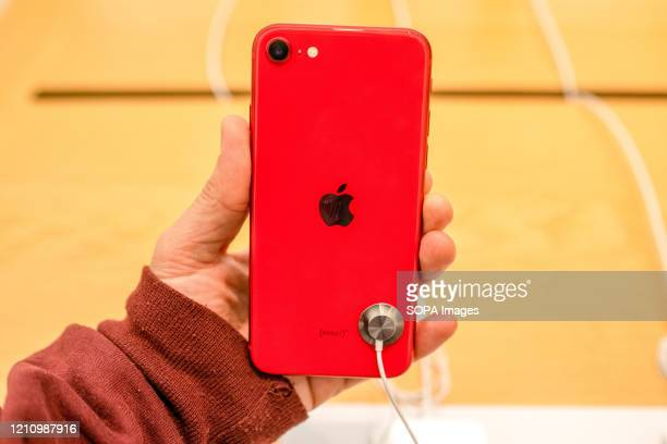 A customer seen holding an iPhone SE red version at an Apple retail store Apple launched sales of its latest iPhone SE around the world