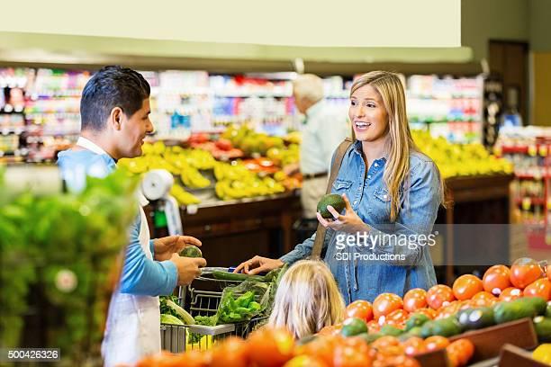 お客様を新鮮な食材を話すスーパー従業員に