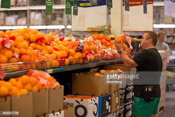 A customer selects a bag of oranges from a sales display inside a supermarket in Moscow Russia on Friday Aug 8 2014 Russia's President Vladimir Putin...