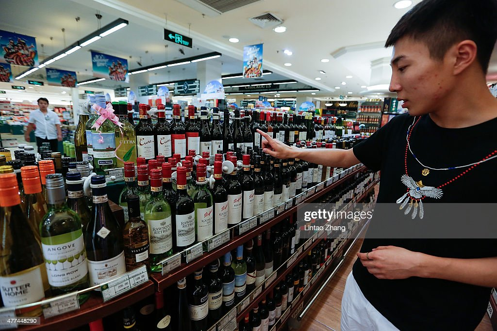 A customer selects a bottle of Australian wine at a supermarket on June 17, 2015 in Beijing, China. China's Minister of Commerce Gao Hucheng today is in Australia to formalise the free trade agreement between Australia and China, In the field of goods, both sides have accounted for 85.4 percent of export trade products will achieve zero tariffs immediately upon entry into force of the Agreement.