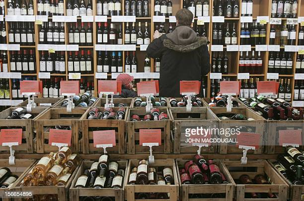 A customer selects a bottle of organic wine or biowine for sale at Berlin's LPG Bio Markt supermarket Europe's largest supermarket for organic and...