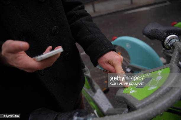 A customer selects a model of Paris' new Velib bicyclesharing service operated by FrancoSpanish consortium Smovengo at a station on January 1 2018 in...