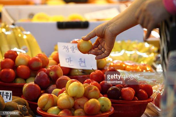 Customer selects a plum at Noeun Agricultural and Marine Products Wholesale Market in Daejeon, South Korea, on Tuesday, July 16, 2013. South Korea...