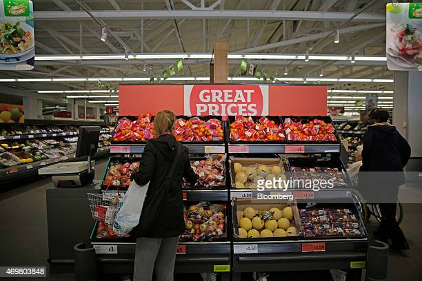 A customer selects apples from a display of fresh fruit inside a Sainsbury's supermarket store operated by J Sainsbury Plc in the Wandsworth district...