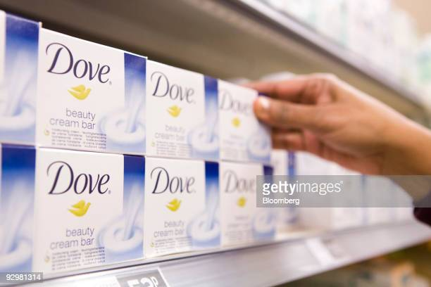A customer selects bar of Dove soap a Unilever Plc product at a Sainsbury's supermarket in London UK on Tuesday Nov 10 2009 Unilever said it cut...