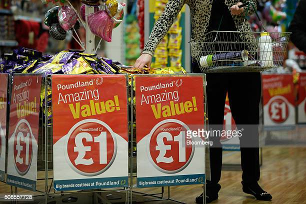 A customer selects chocolate bars from a wire basket bin with a one pound sterling sign attached at Poundland Group Plc store in Leigh UK on Thursday...