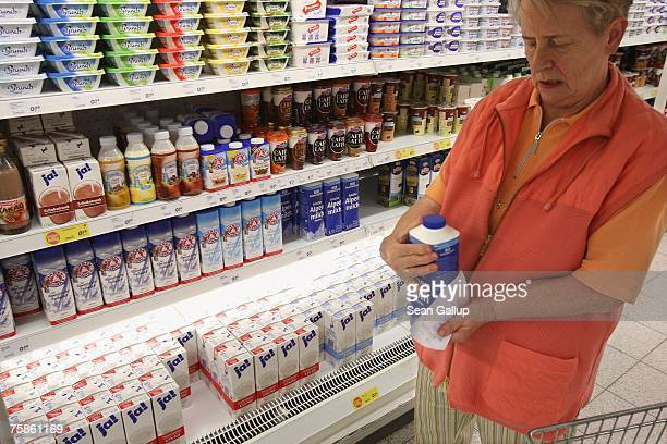 A customer selects milk from a supermarket shelf July 30 2007 in Berlin Germany German milk producers have announced they will raise prices on milk...