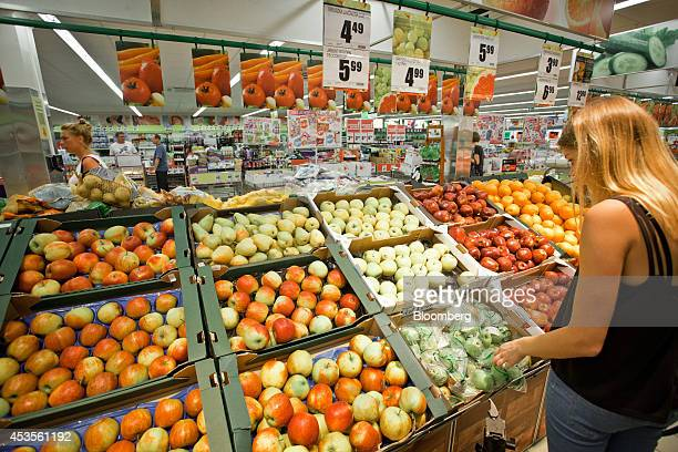 A customer selects Polish apples for sale in the fruit and vegetable section of a Biedronka supermarket operated by Jeronimo Martins SGPS SA in...