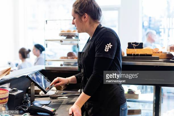 """klantenservice in een kleine plaatselijke bakkerij winkel. - """"martine doucet"""" or martinedoucet stockfoto's en -beelden"""