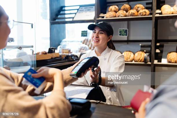 """customer service in a small local bakery shop. - """"martine doucet"""" or martinedoucet stock pictures, royalty-free photos & images"""