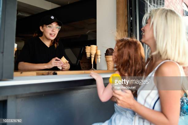 customer service in artisanal ice cream parlor. - ice cream parlor stock photos and pictures