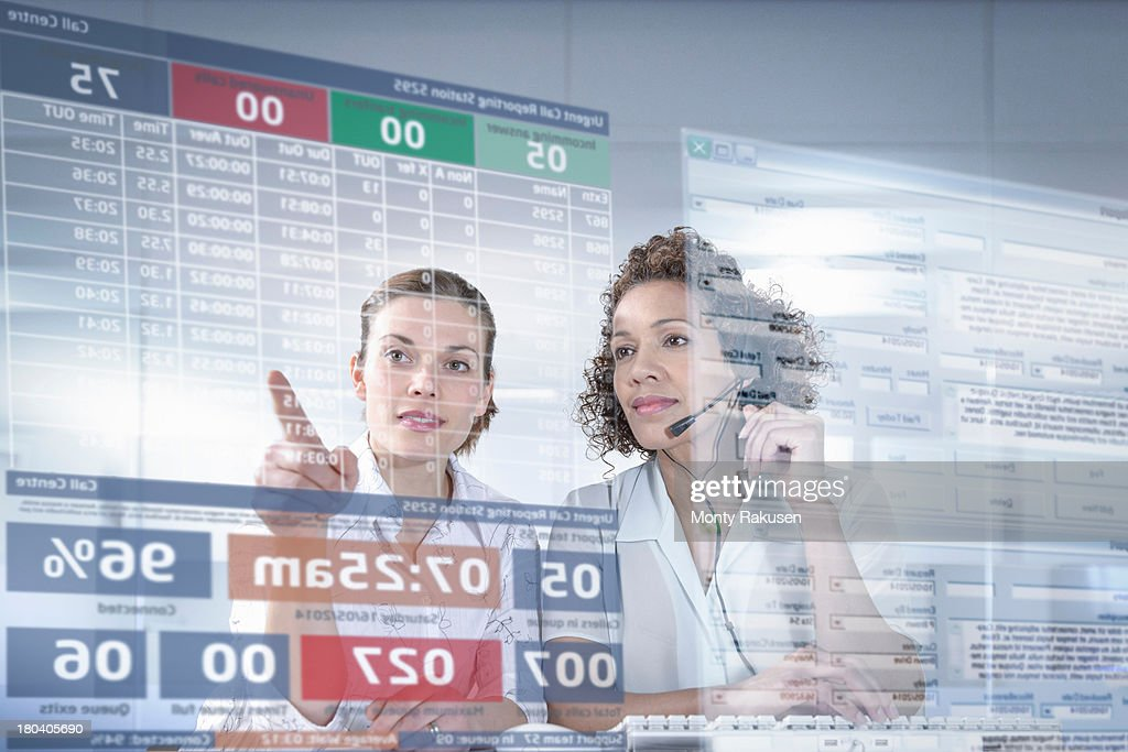 Customer service operators looking at interactive screen : Stock Photo