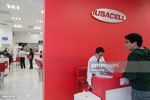 A customer service representative assists a man at a Grupo Iusacell SA customer service center in Mexico City Mexico on Wednesday Oct 1 2014 Japanese...