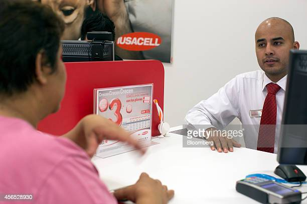 Customer service representative David Hernandez assists a woman at a Grupo Iusacell SA customer service center in Mexico City Mexico on Wednesday Oct...