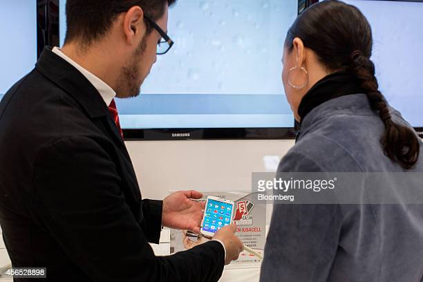 A customer service representative discusses a Samsung mobile phone with a woman at a Grupo Iusacell SA customer service center in Mexico City Mexico...