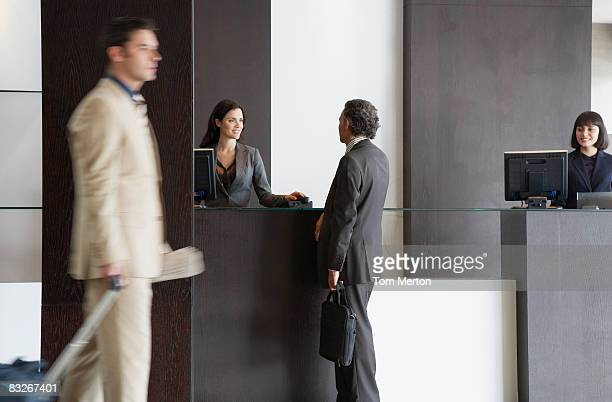 customer service representative helping businessman - hotel lobby stock pictures, royalty-free photos & images
