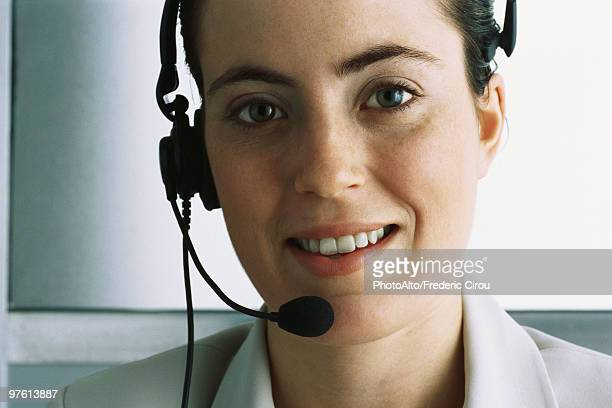 Customer service representative wearing headset, smiling at camera