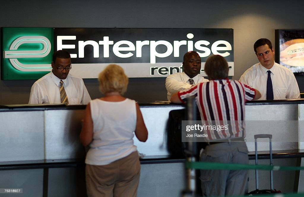 Customer service representatives Oneal West (L-R), Marmontel Michel and Benjamin Meyer wait on customers at Enterprise rent-a-car at the Fort Lauderdale/Hollywood International airport July 10, 2007 in Fort Lauderdale, Florida. Pending regulatory approval, expected in the next month, Enterprise will buy National and Alamo rental car companies. Enterprise would make an instant jump from about 8% of the airport car rental market market to more than 27% just behind Hertz's 28.5%.