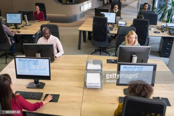 customer service representatives working in call centre - outbox filing tray stock pictures, royalty-free photos & images