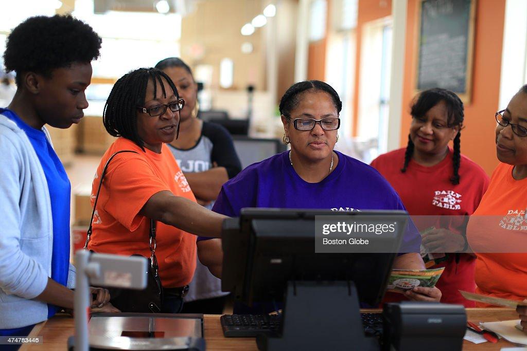 Customer Service Supervisor Angelina Latimore, left, in orange