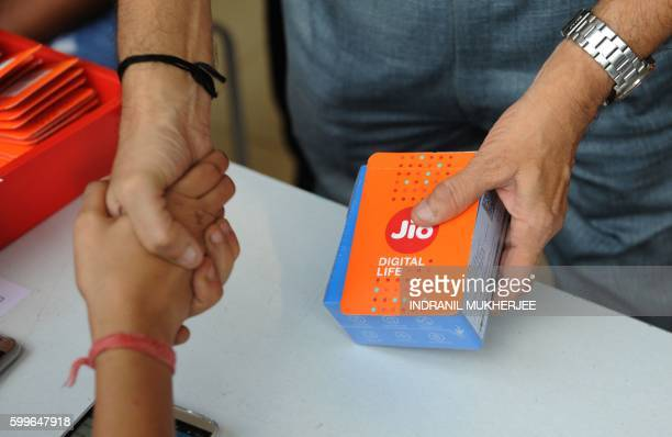 A customer shakes hands with a store employee after purchasing a Reliance Jio Infocomm 4G mobile services connection in Mumbai on September 6 2016...