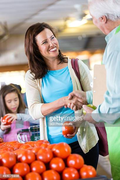 Customer shaking hands with senior grocery store owner