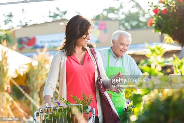 Cliente para plantas de compras en la tienda de jardín al aire libre o en el mercado