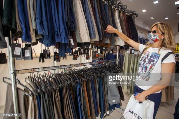 A customer shops at a clothing store on May 23 2020 in Matera Italy Restaurants bars cafes hairdressers and other shops have reopened subject to...
