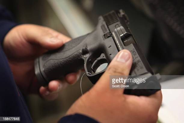 Customer shops for a pistol at Freddie Bear Sports sporting goods store on December 17, 2012 in Tinley Park, Illinois. Americans purchased a record...