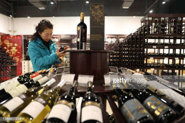 Customer shops for bottles of wine at a store in the Qingdao Area of China Pilot Free Trade Zone on December 1, 2020 in Qingdao, Shandong Province of...