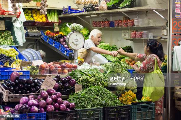 A customer shops for fruit and vegetable produce at an indoor market in Rome Italy on Thursday Aug 17 2017 Italy's economic recovery extended for a...
