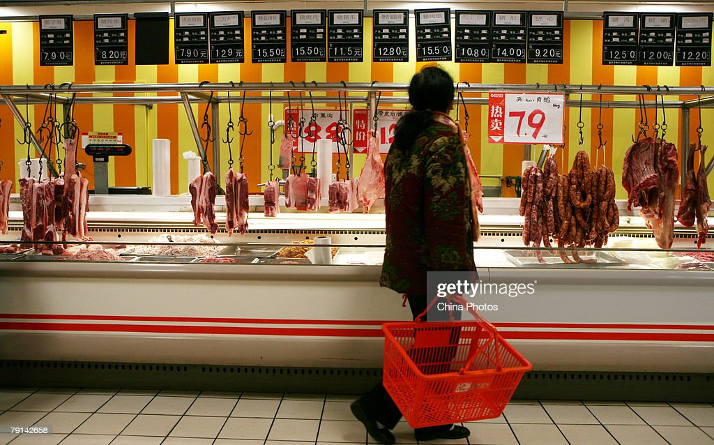 A customer shops for meat at a supermarket on January 20, 2008 in Chongqing Municipality, China. The National Development and Reform Commission, the country's pricing authority, issued price controls on a number of daily necessities, including grain, edible oil, meat, milk, eggs and liquefied petroleum gas last week to bring rising inflation under control.