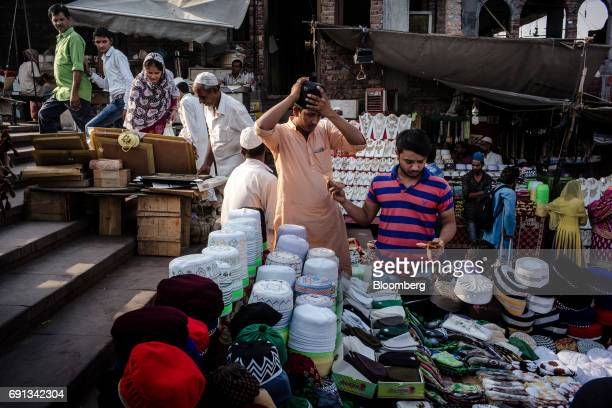Customer shops for skullcaps at a stall outside the Jama Masjid during the Muslim holy month of Ramadan in the Old Delhi area of New Delhi, on...