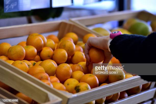 A customer shops for tangerines in an organic supermarket in Saintes western France on October 23 2018 According to the public information platform...