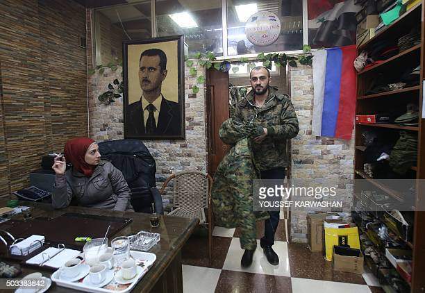 A customer shops in 'Commandos' a shop that sells militarystyle clothing and accessories in the Syrian coastal city of Latakia on December 19 2015...