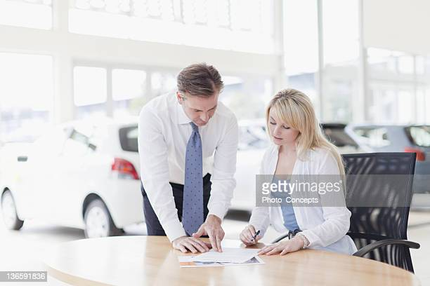 Customer signing at car dealership