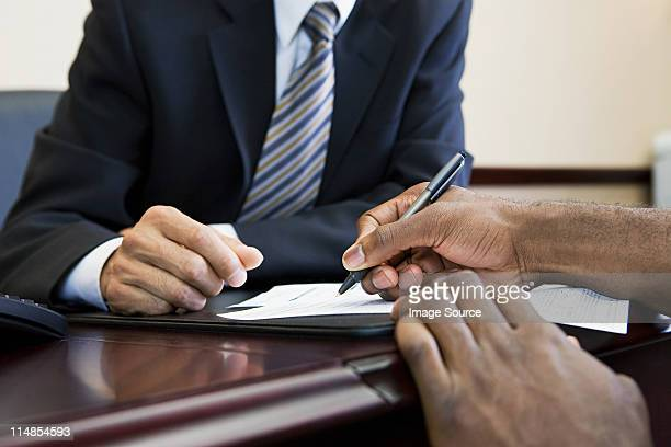 customer signing paperwork with bank manager - loan stock pictures, royalty-free photos & images