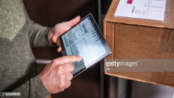 customer signing receipt of home delivery on a tablet - correspondence stock pictures, royalty-free photos & images