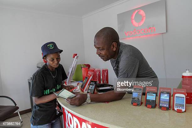 A customer signs up for an Mpesa mobile payment account at a phone store operated by Vodacom Group Ltd in the Alexandra township in Johannesburg...