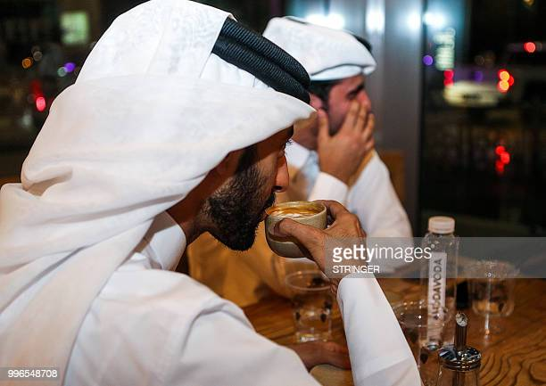 A customer sips a cup of coffee as he sits in the 'Flat White' cafe in the Qatari capital Doha's Tawar Mall on June 8 2018 Tawar Mall looks like any...
