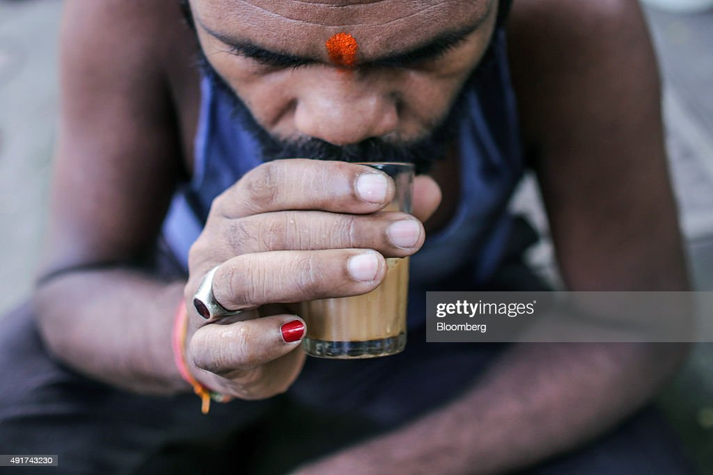 A customer sips a glass of chai at a roadside stall in Mumbai, India, on Friday, Sept. 25, 2015. Chai, the sweet, milky tea concoction popular in most of South Asia, is getting an image makeover in India. Rising incomes and demand for a refined tea experience transcending chai are spawning posh tea lounges in the nation's biggest cities. Photographer: Dhiraj Singh/Bloomberg via Getty Images